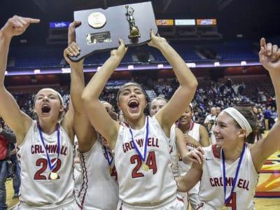 girls basketball team raising trophy up